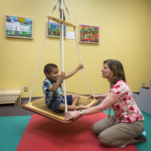 Clinics - boy on swing with therapist